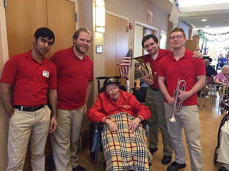Steven and members of his ensemble pose with a military veteran following a performance