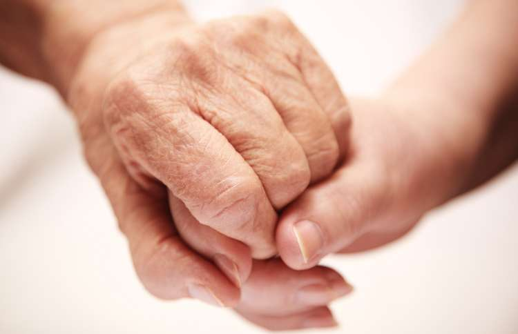 Guideposts: An older woman's hand is comforted by the clasp of a young woman's hand