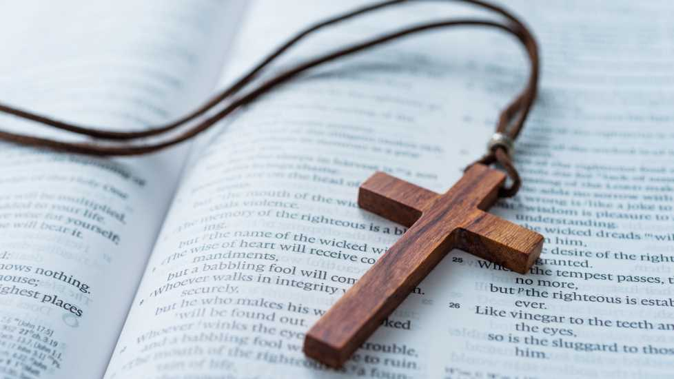 A necklace with a prayer cross resting on a Bible.