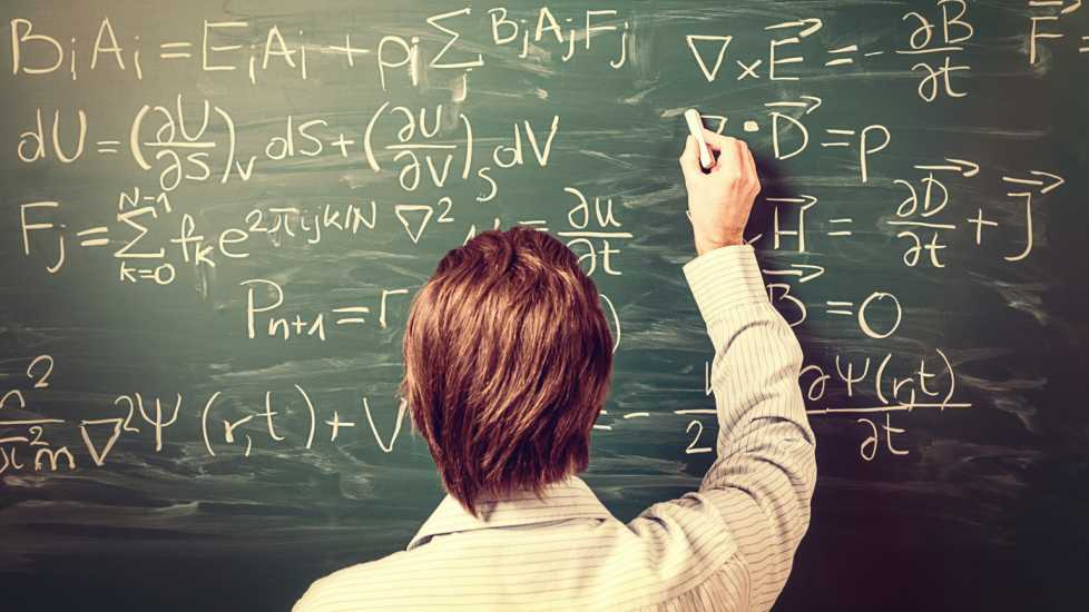 A man solves physics equations on a chalkboard.