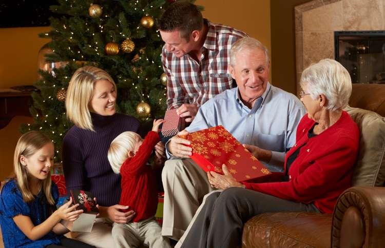 Guideposts: Children, parents and grandparents exchange gifts under a Christmas tree