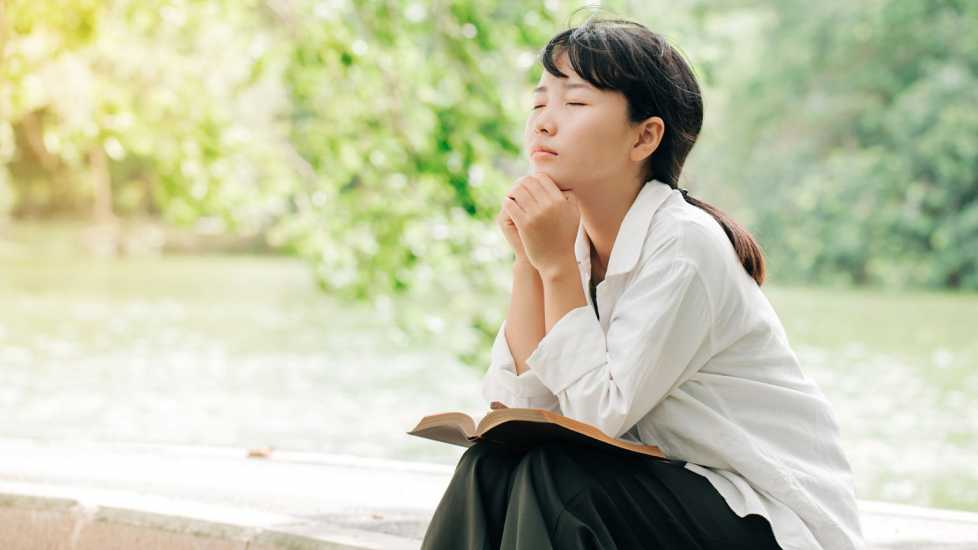 A woman praying; Getty Images