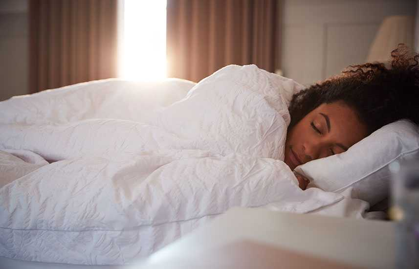 Woman sleeping as day breaks through curtains