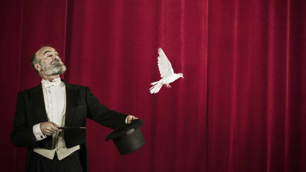 Magician performing stage magic with doves.
