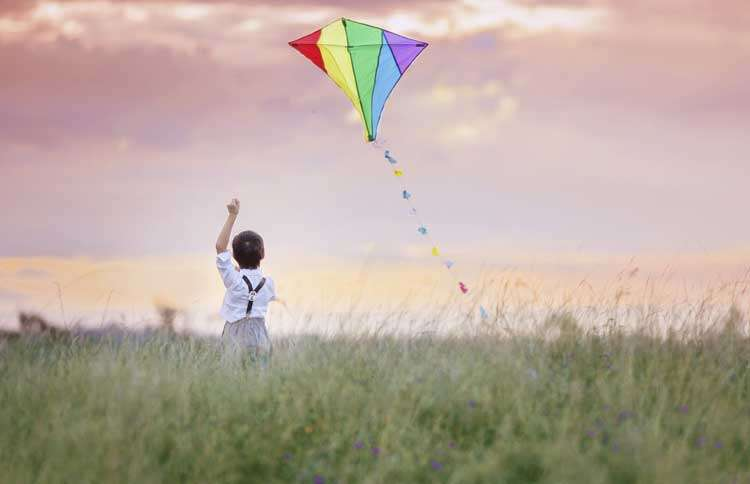 Guideposts: A young boy stands in a field, his hands tightly clasped on the string of a kite that floats above him