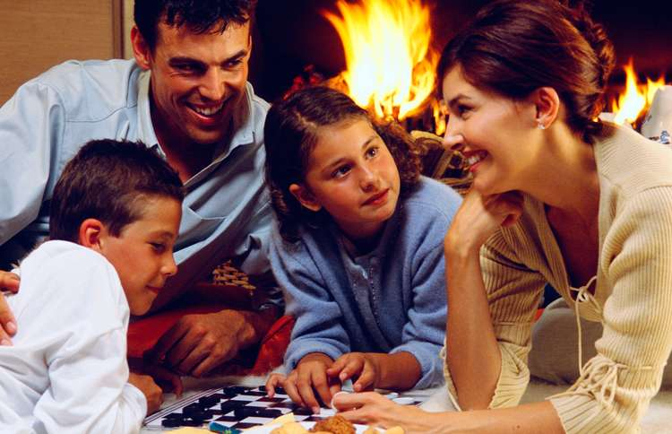 Guideposts: A family huddles around a checkers board in front of a roaring fire