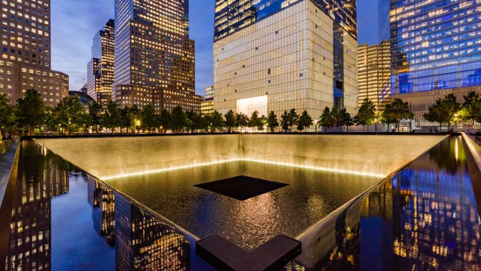 The North Reflecting Pool illuminated at twilight with view of One World Trade Center. Lower Manhattan, 911 Memorial & Museum, New York City (Alamy)