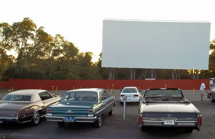 Three classic cars parked in the lot at Cape Cod's Wellfleet Drive-in