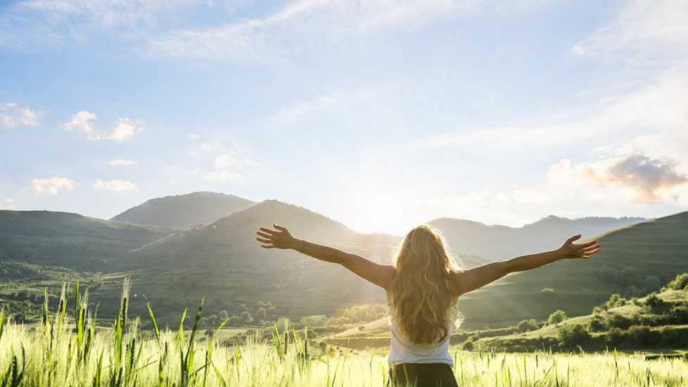 Woman in nature with hands outstretched having a beautiful fresh morning (Getty Images)