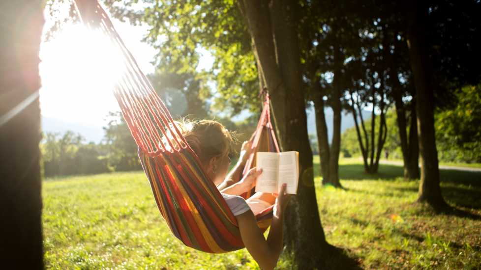 Woman on hammock at sunset reading book (Getty Images)