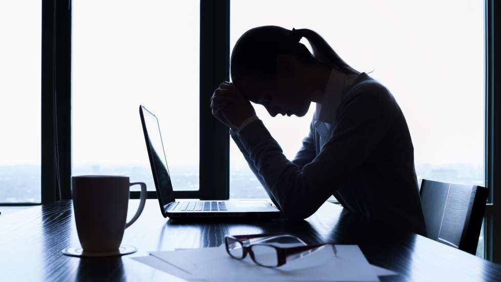 a woman sits in shadows at a table and her hands are folded in prayer over an open laptop