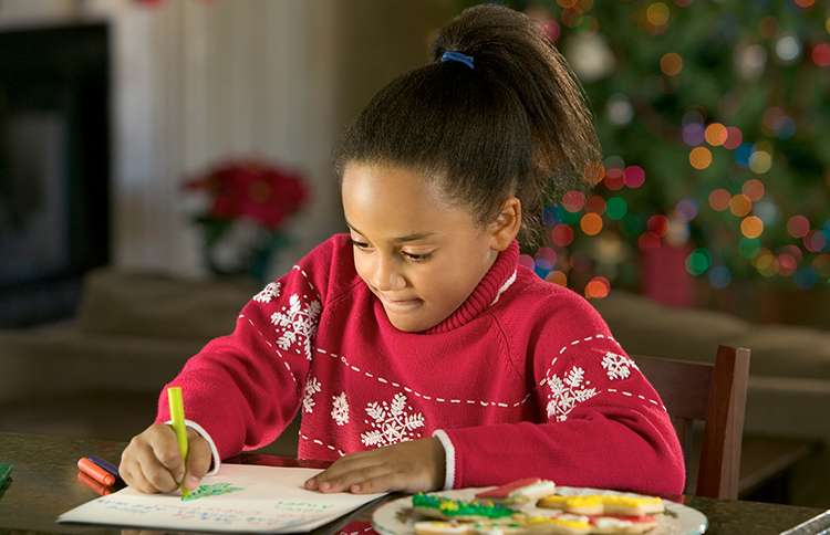 A young girl composes a letter to Santa Claus