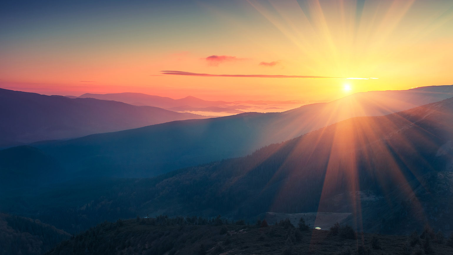 The sun rises over mountaintops