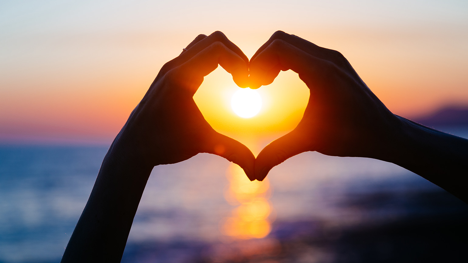 A pair of hands form a heart with a sunset in the background