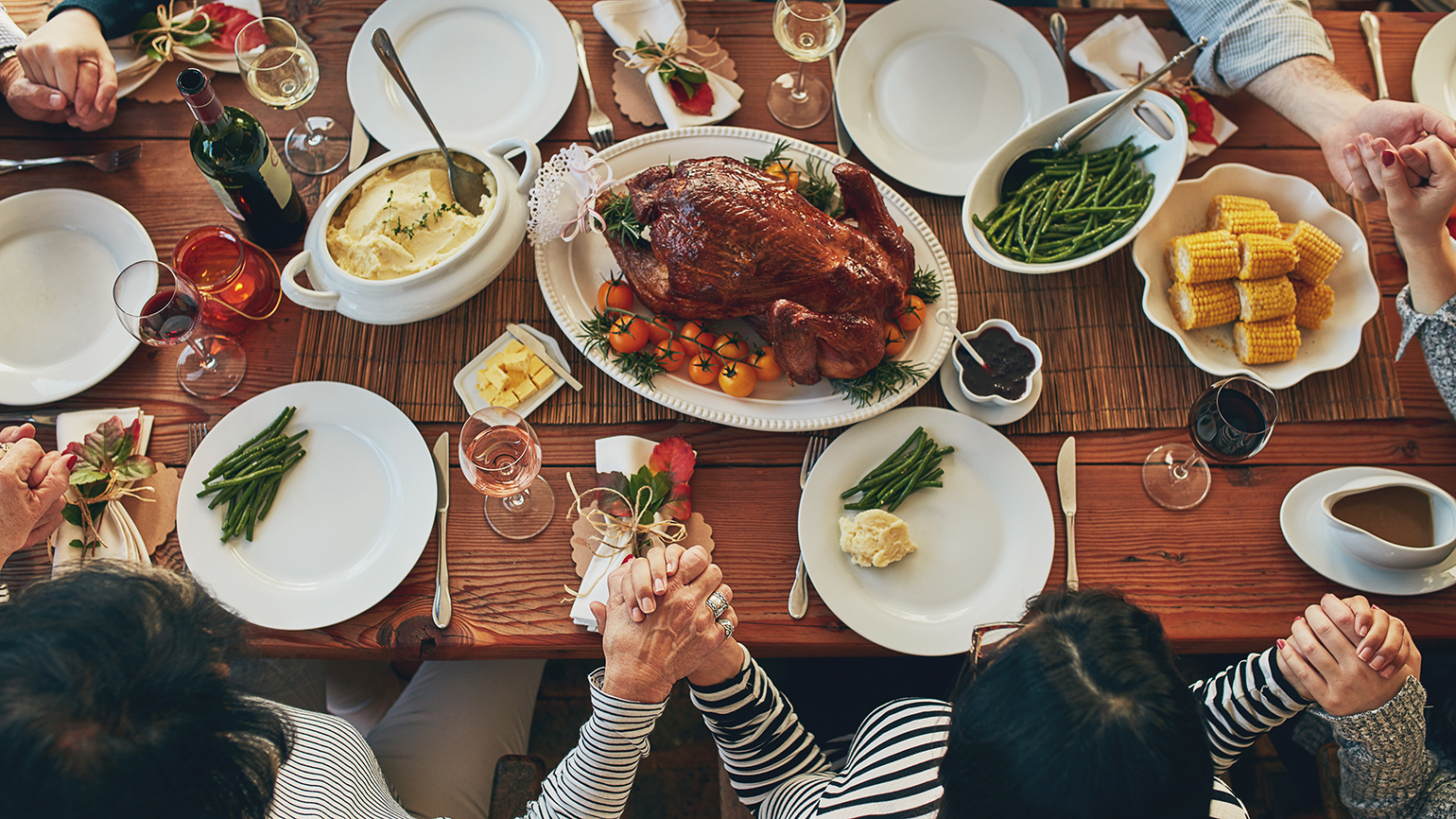 A family clasps hands in prayer at the Thanksgiving table