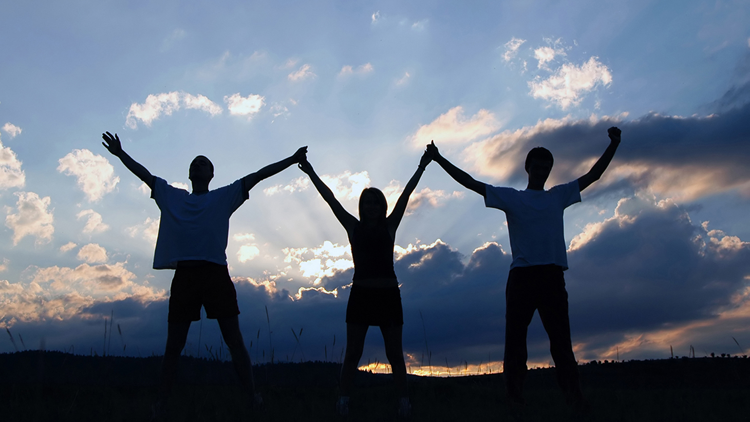 Three people holding hands up to the sky