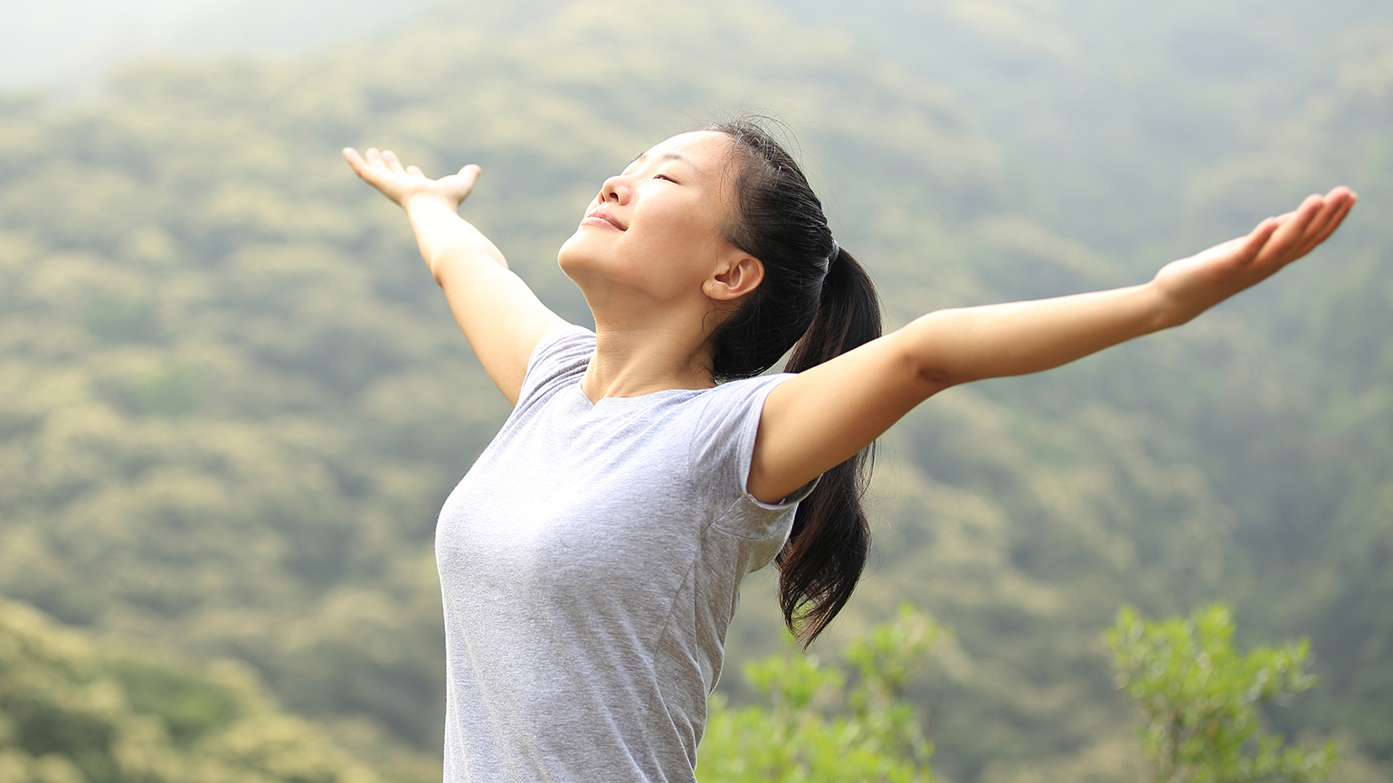 Woman with arms outstretched to the sun