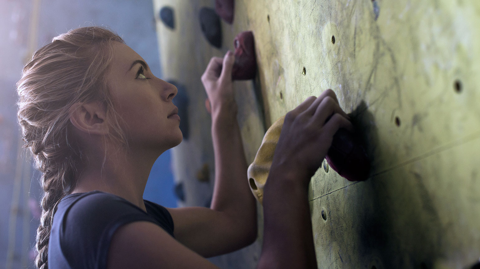 A woman pauses while climbing wall