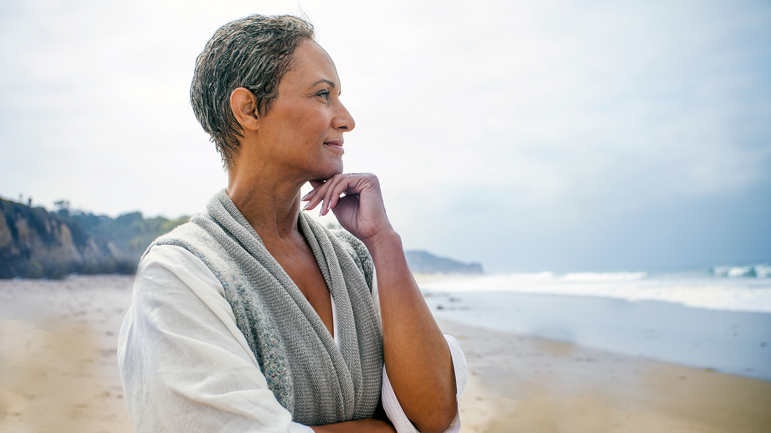 A contented woman gazes thoughtfully out at the ocean