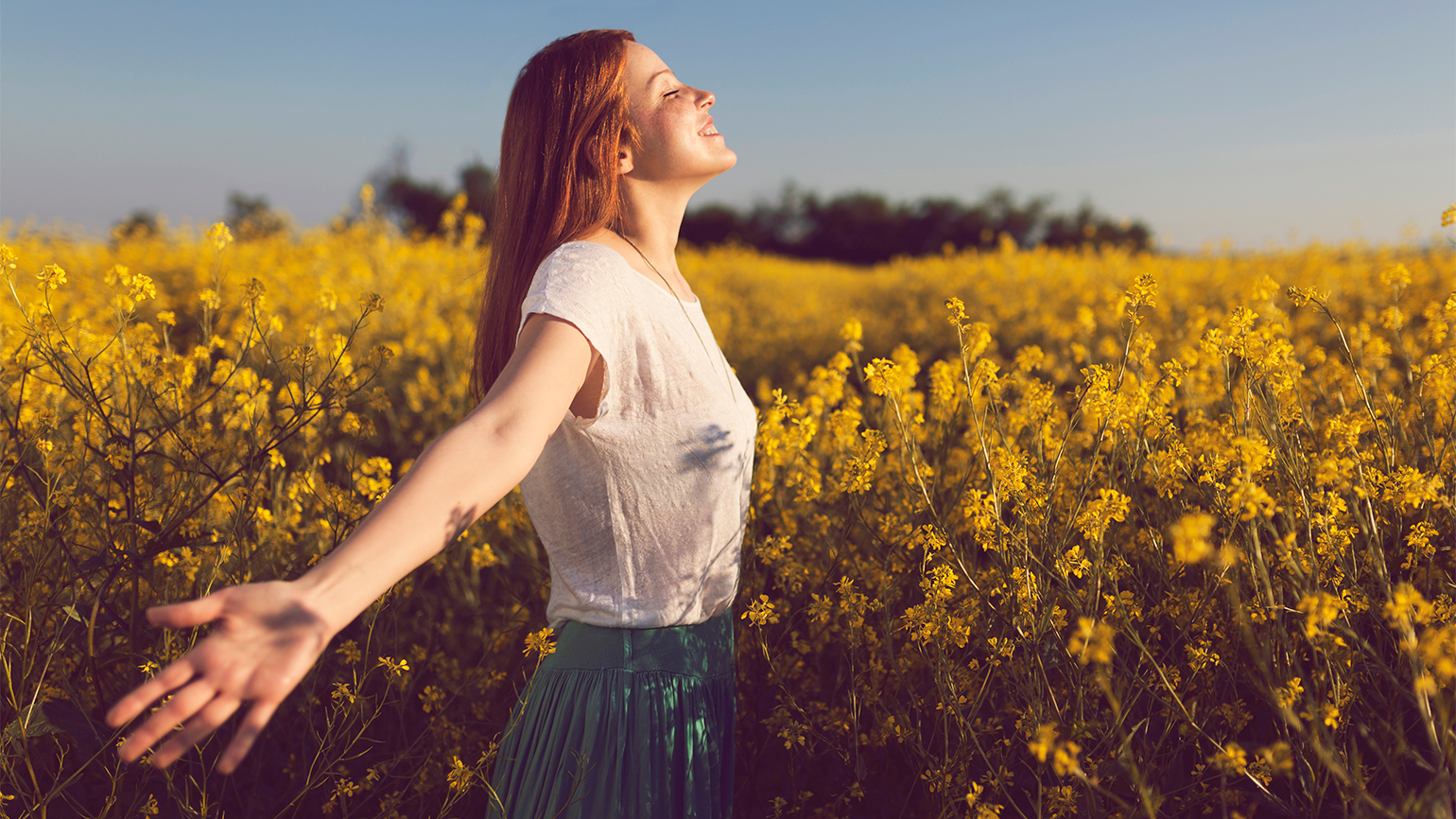 A woman with outstretched arms stands in a field of spring flowers