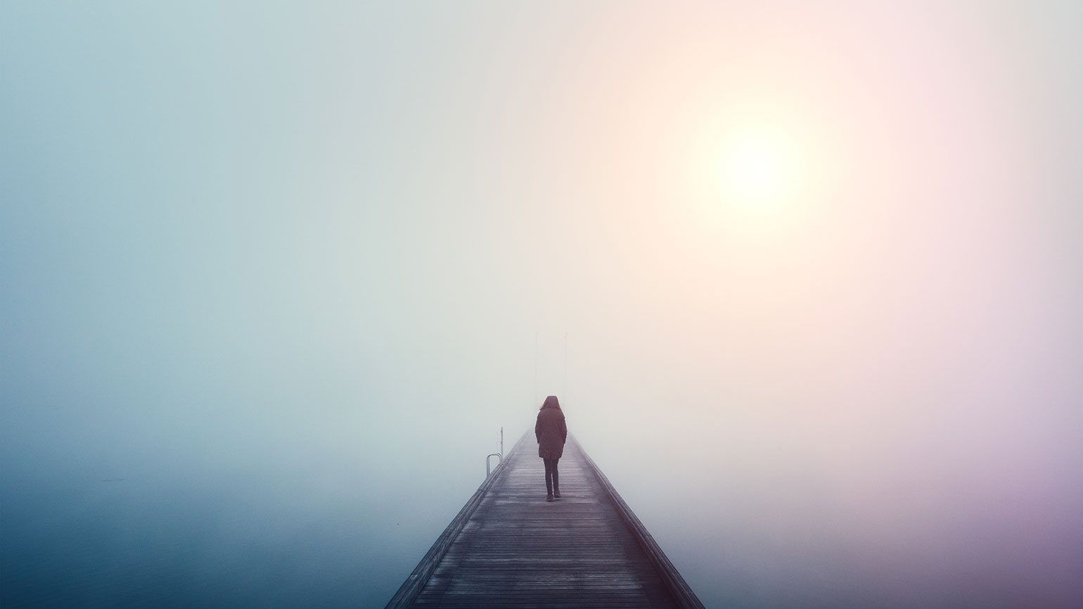 A woman stands at the far end of a pier on a foggy lake