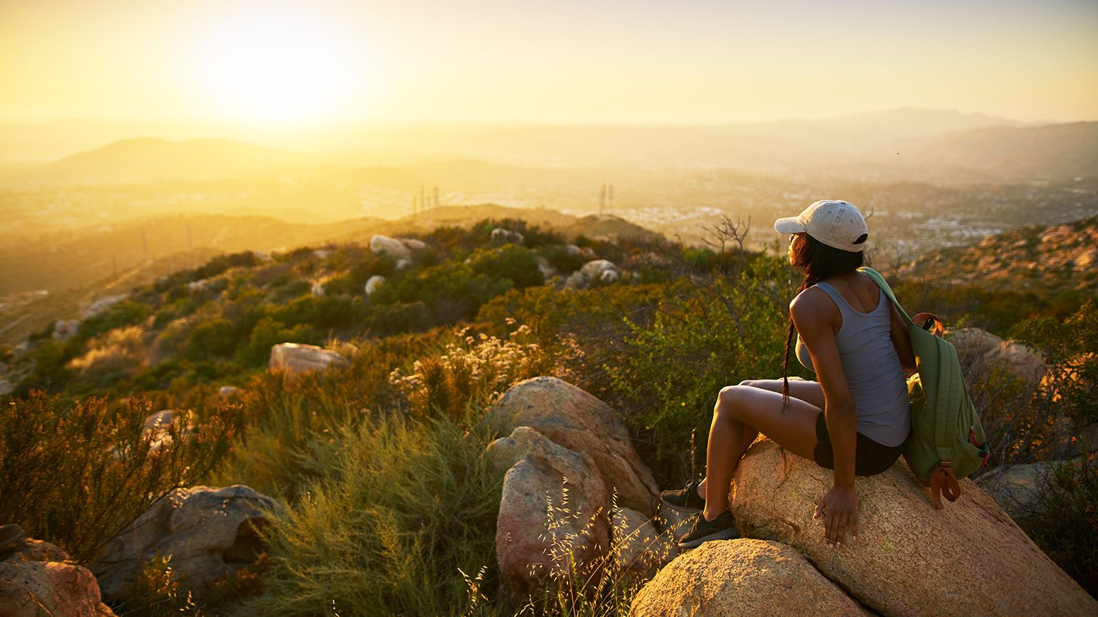 A woman greets the sunrise from a hilltop