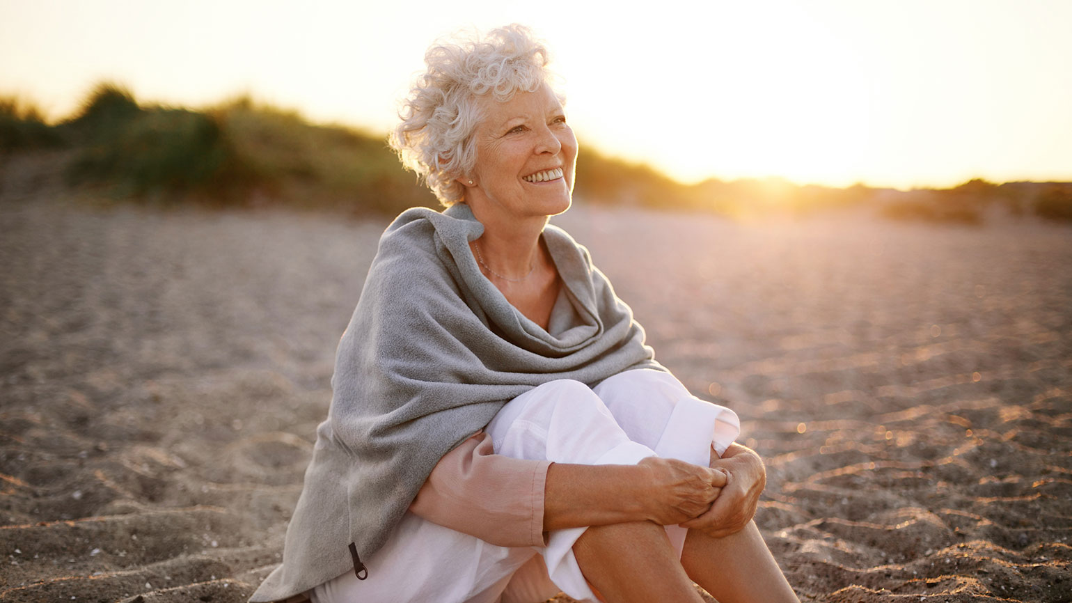 A contented woman greets the sunrise on a beach