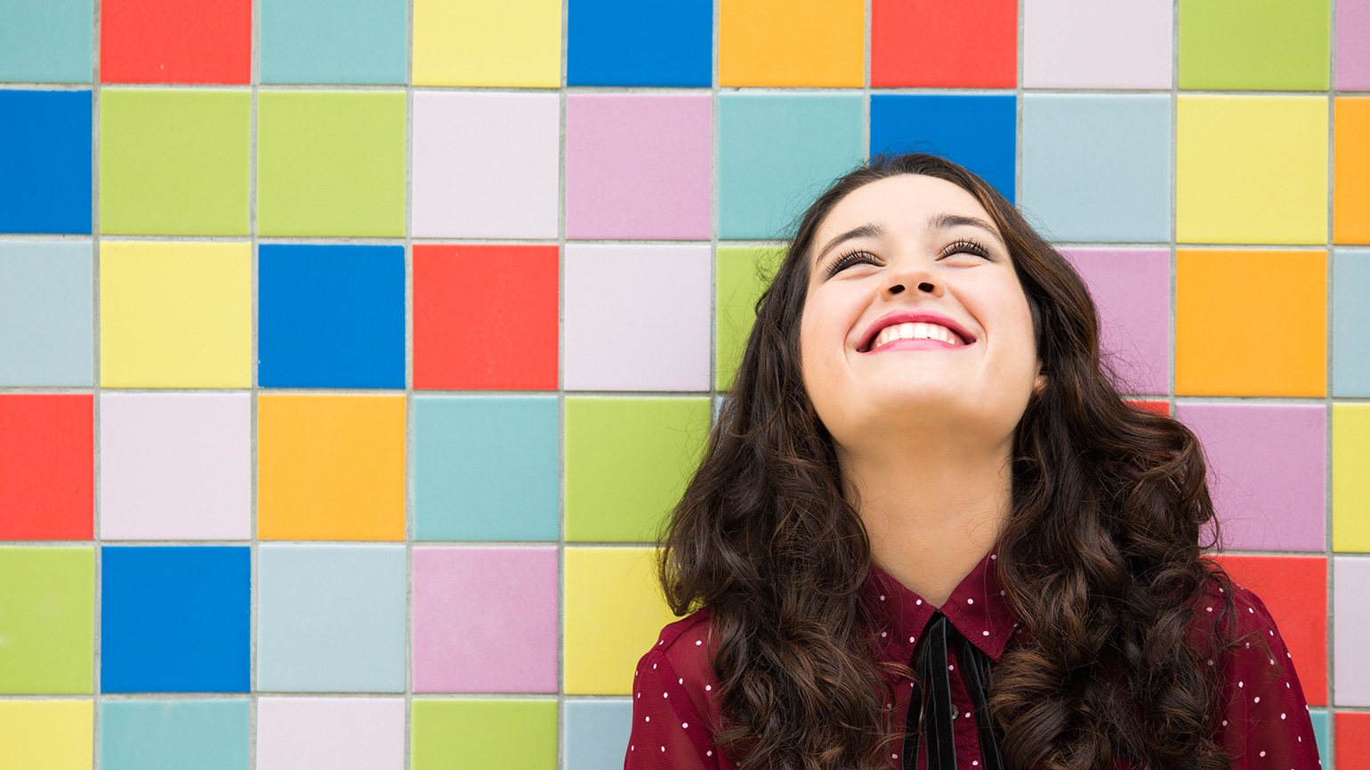 Smiling woman standing in front of colorful tiles