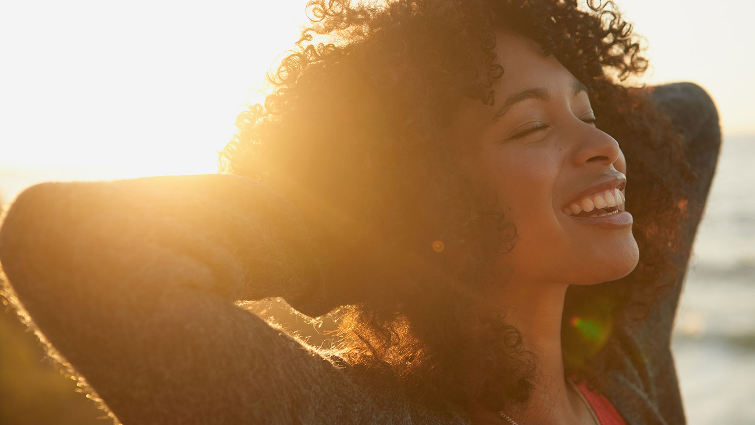 A young woman smiles contentedly on a bright sunny day