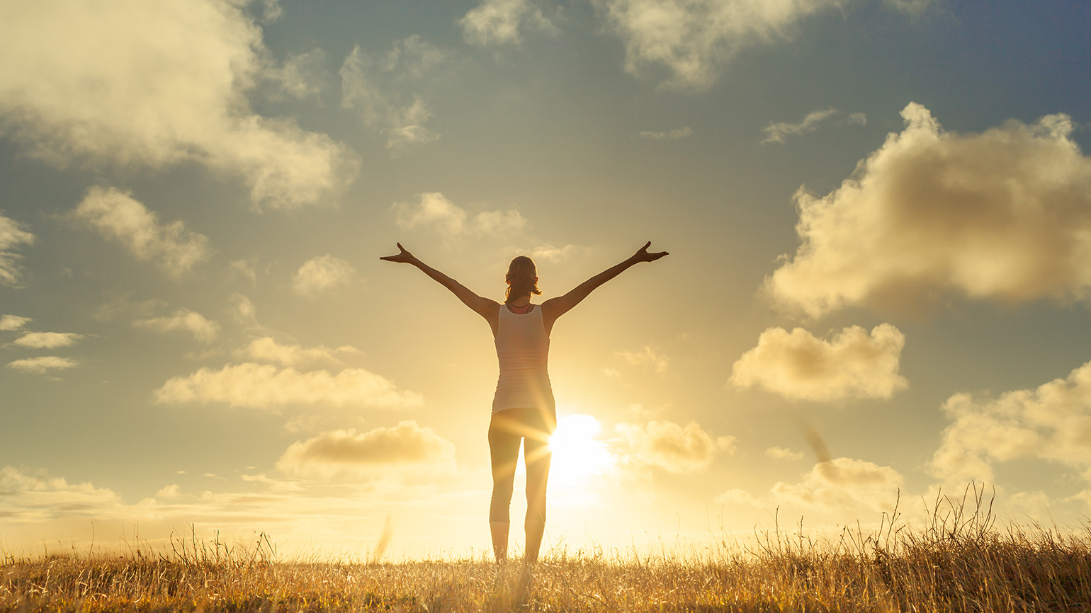 A woman greets the sunrise, arms upraised