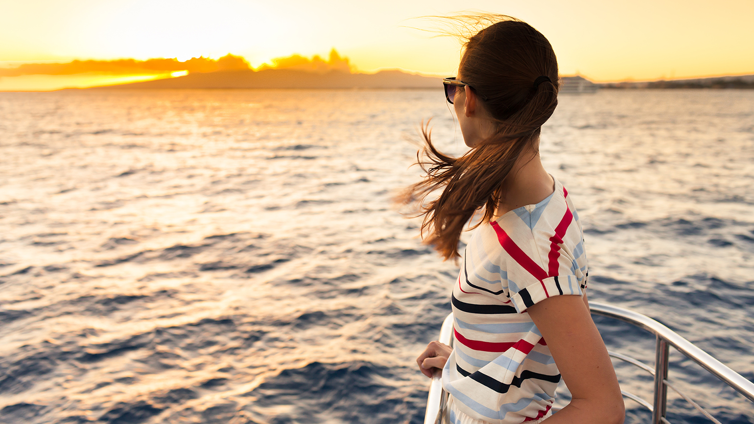 A woman on a ferry looks out at the sunrise