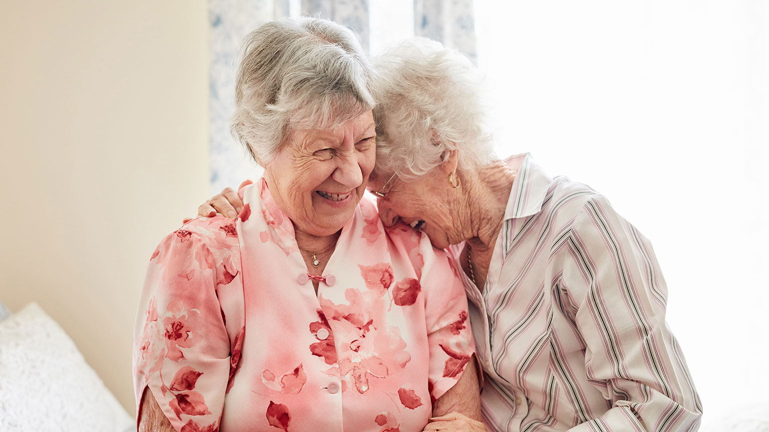 Two senior women forget their differences and laugh together