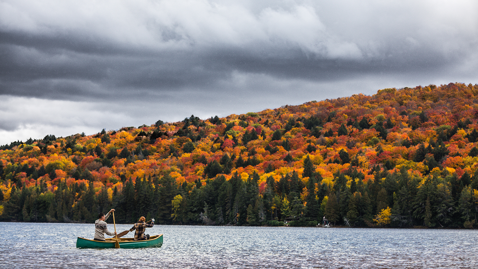 A couple in a canoe on a mountain lake in autumn
