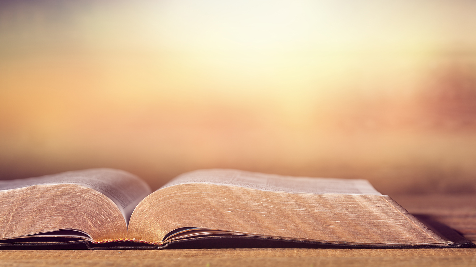 Open Bible on wooden table at sunrise