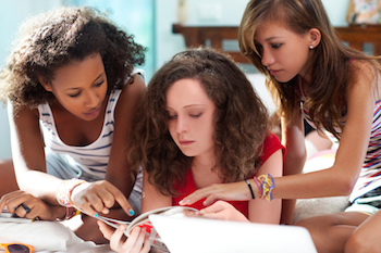 Teen girls looking at a fashion magazine. Photo from 123RF(r)