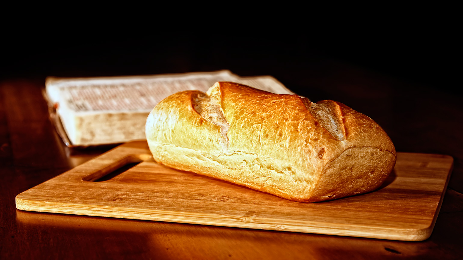 A loaf of fresh-baked bread rests by an open Bible