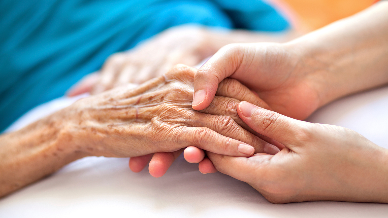 A senior woman's hands are clasped in the hands of a younger caregiver