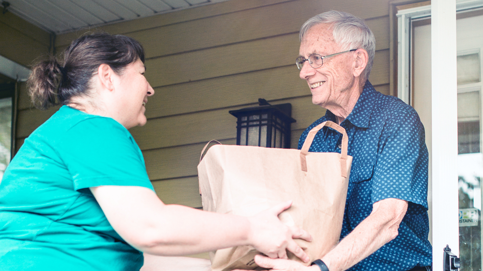 A woman brings a bag of groceries to her senior neighbor