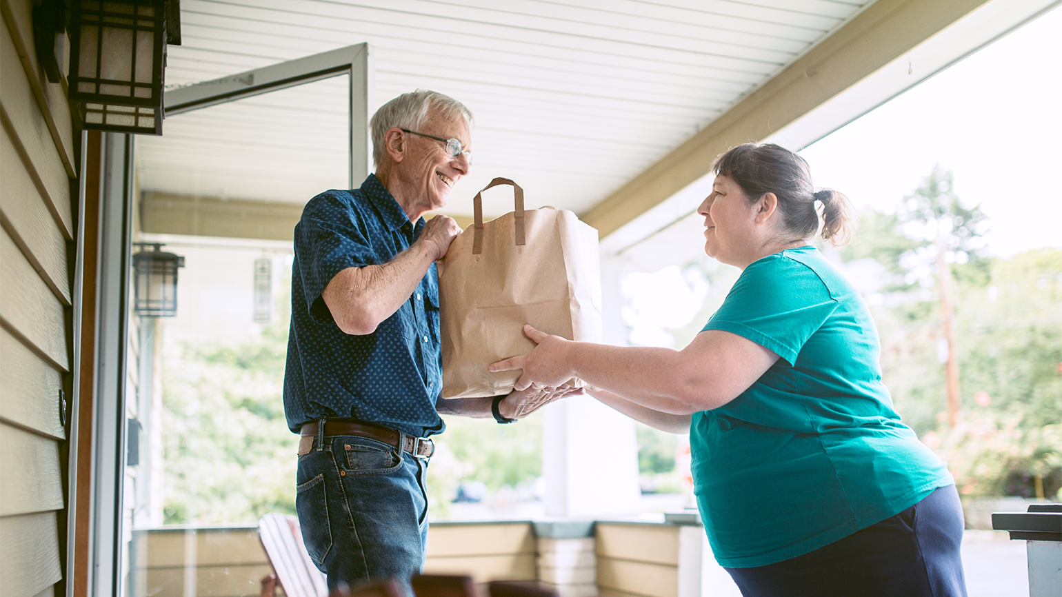 A woman brings groceries to a senior neighbor