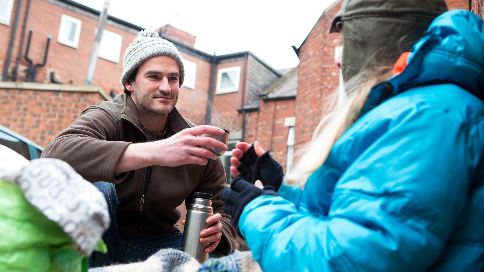 A man gives food to a homeless person