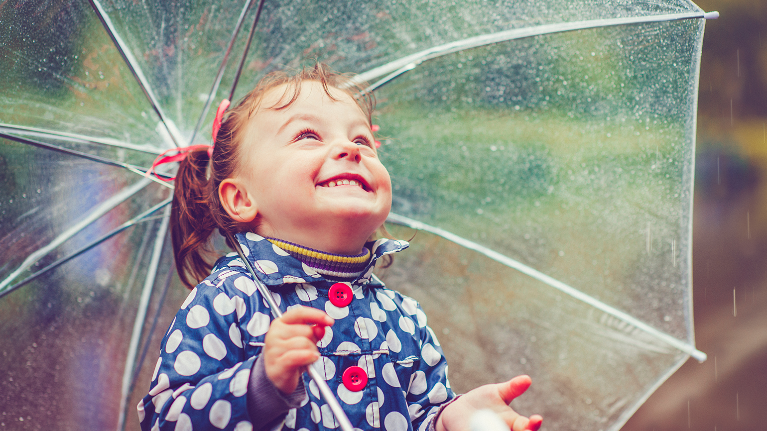 A child with an umbrella looks up at the raindrops and smiles