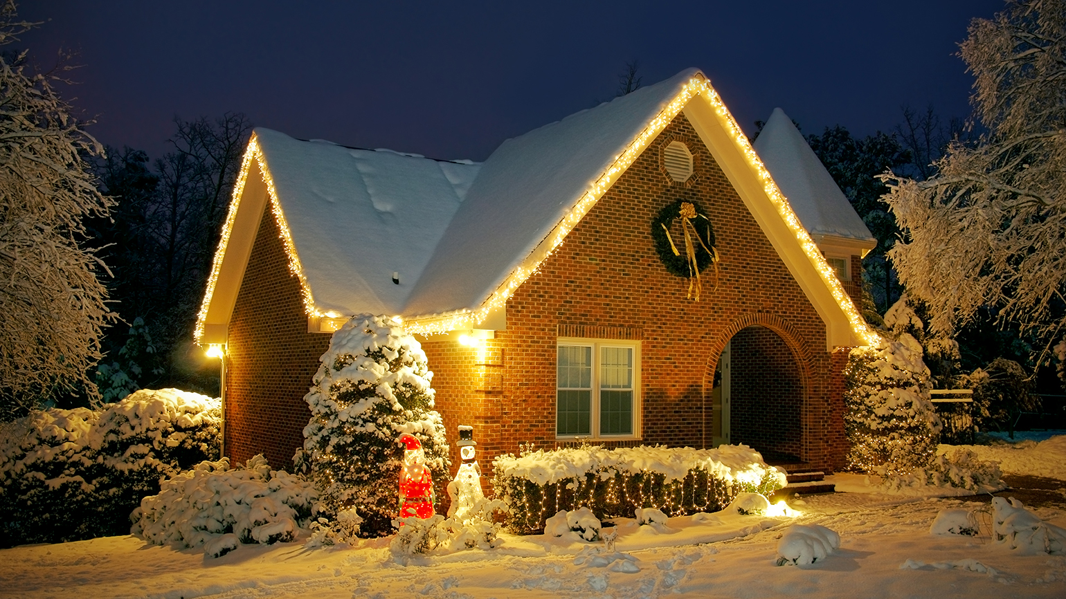 A modest warmly illuminated by Christmas lights