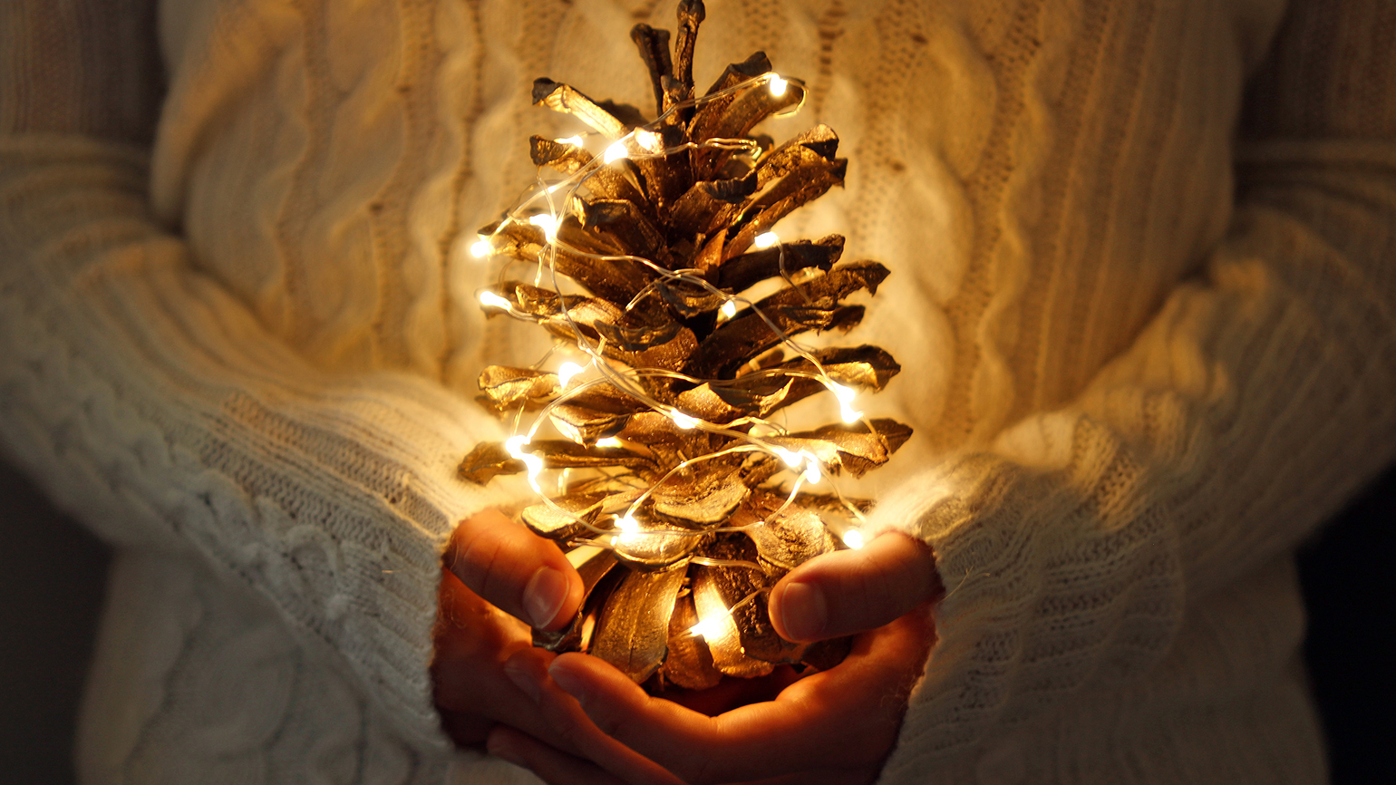 A woman's hands hold a large pine cone decorated like a Christmas tree