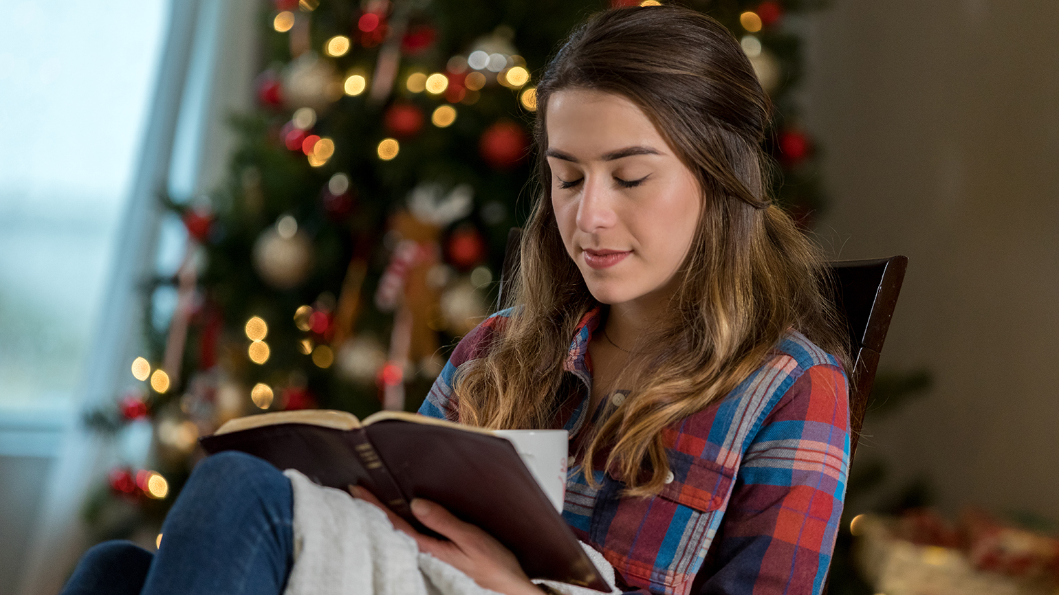 A woman prays over her open Bible at Christmastime