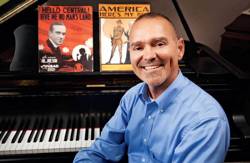 Bobby Simma sits at a piano with several copies of sheet music