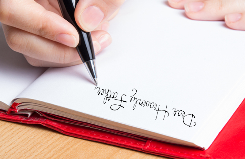 A young woman's hands are seen writing in a diary.