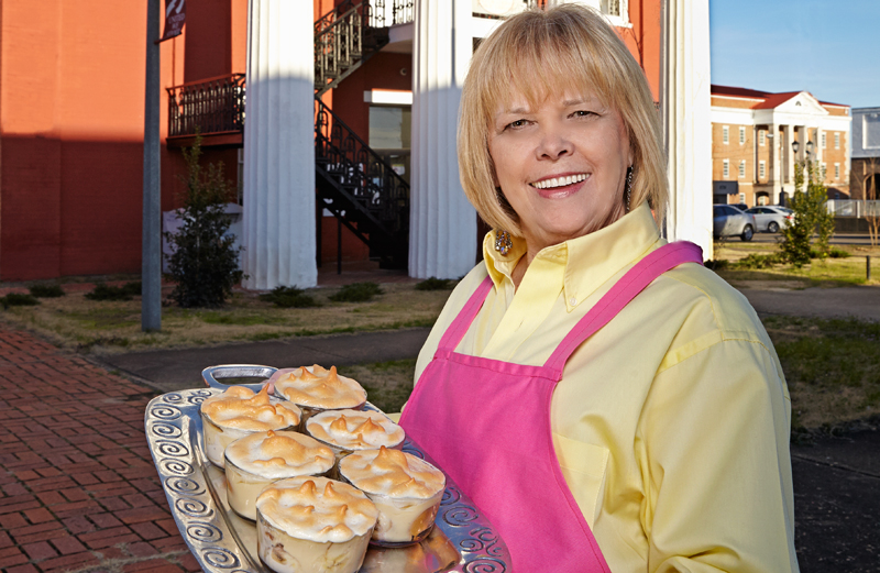 A smiling Adrian Drinkard holds a tray of small banana puddings.