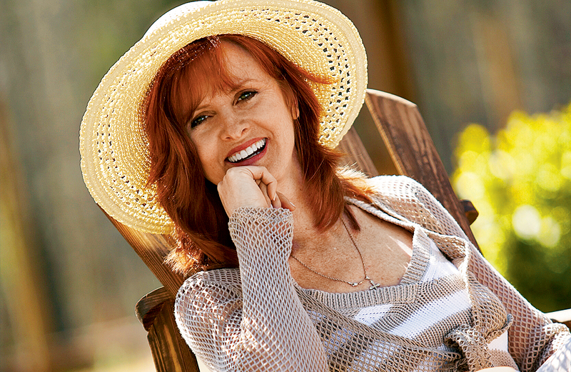 Julie Garmon smiles under a wide-brimmed straw sun hat.