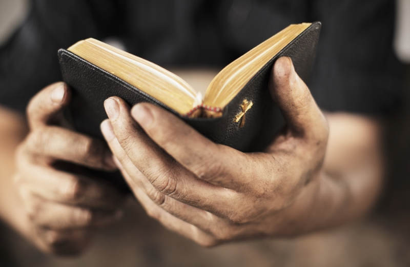Close-up of a man holding the Bible
