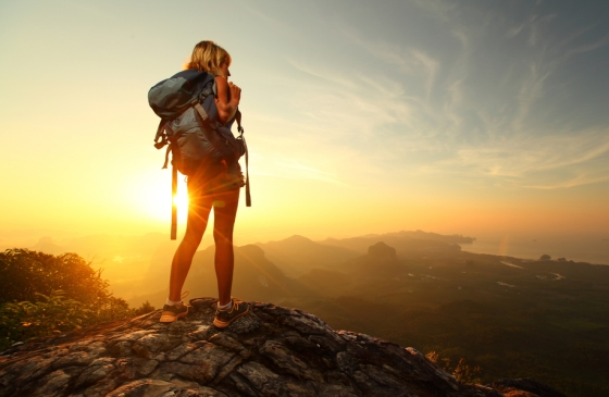 Woman on top of a mountain looking at the sunrise.
